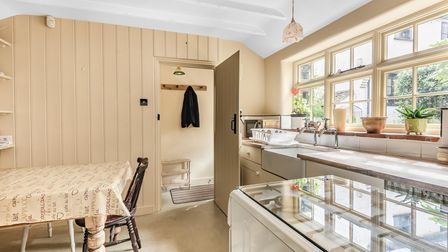 Cream coloured Shaker-style kitchen with wood panelling, Butler style sink, raised countertops and wide window