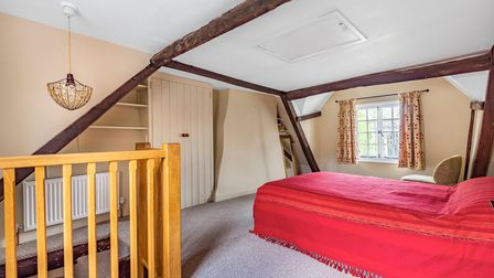 Double bedroom with sloping ceilings, sash window, timber beams and alcove storage with hanging chandelier