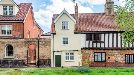 17th century timber-framed townhouse in a row with Tudor detailing, pathway in front, lawn outside