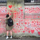 A woman writes in a heart on the National Covid Memorial Wall on the Embankment in London to after t