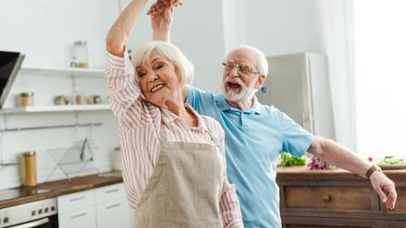 Selective focus of smiling senior couple dancing in kitchen