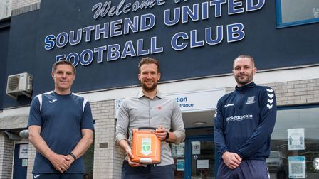 Charlie Edinburgh (middle) donating adefibrillator to Southend United