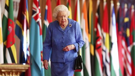 Queen Elizabeth II walks past Commonwealth flags in St George's Hall at Windsor Castle , to mark Com