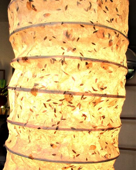 Lamp shade of handmade paper detailed with flower petals and bamboo