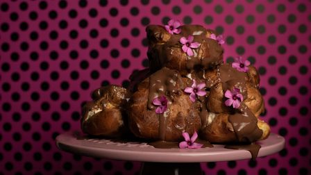 A tower of profiteroles with chocolate sauce and flowers