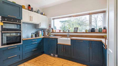 Contemporary Shaker-style kitchen with blue cabinets, Butler sink, large window, wooden floor