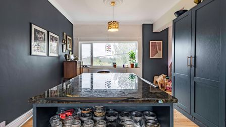 Contemporary dark blue kitchen with gallery wall, leopard print light fitting and large window