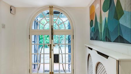 Arched entrance door with bolts and spacious entrance hall with white radiator cover and abstract painting