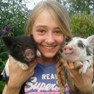 Megan Clarke holding up her pets pigs Tammy and Ruby