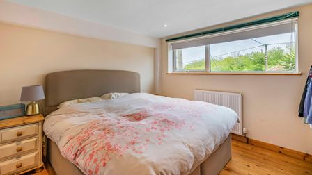 Contemporary bedroom with double bed, neutral decoration and wide windows offering views over village