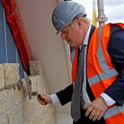 Prime Minister Boris Johnson helps to lay bricks in a wall during a visit to a construction site in Cheshire.