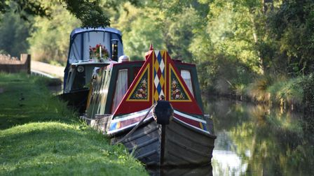 two canal boars moored on a grass bank by a river