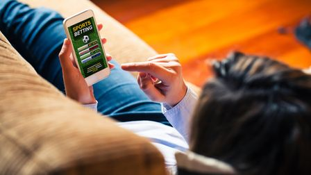 Woman holding a mobile phone to visit a sports betting website while lies down at home.