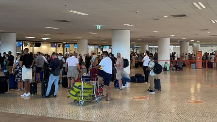 Passengers queue for the Ryanair and easyJet check-in desks at Faro airport in Portugal