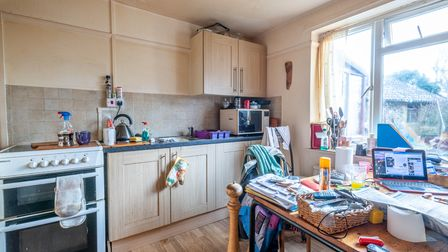 Dated 1970s style kitchen with base and wall units, cooker, kitchen table, window and lino floor