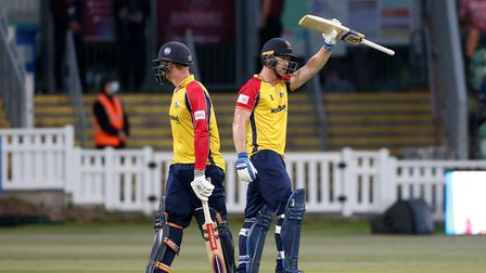 Jimmy Neesham raises his bat to celebrate reaching his fifty for Essex against Somerset