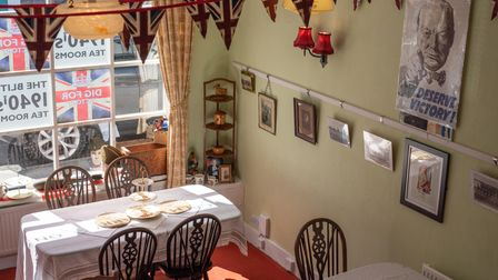 The front room on the ground floor is adorned with bunting, posters, and photos of real wartime soldiers