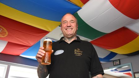 The Railway Tavern's Paul Summers underneath a selection of flags representing Euro 2020 sides