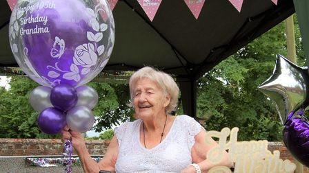 Birthday girl Florence Many with her balloons and cake