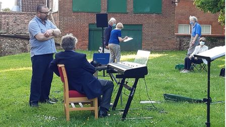 Members of the Fakenham Choral Society singing together in the town's parish churchyard.