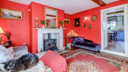 Period-style sitting room with walls painted bright red, a woodburner set into an ornate fireplace, velvet chaise longue