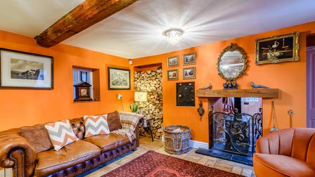Reception room with exposed timber beams, open hearth with wood burner, bright walls painted orange