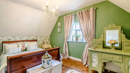 Large double bedroom with wooden sleigh bed, walls painted green, ornate vanity unit and windows with pink curtains