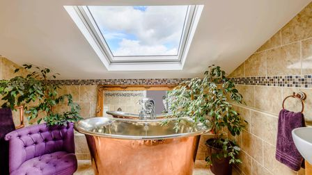 Free-standing copper bath beside plush velvet arm chair under a skylight in bathroom with plants either side