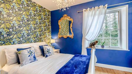 Large double bedroom with tropical style wallpaper, wall painted bright blue and hanging sparkly chandelier