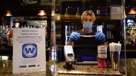 File photo dated 04/07/2020 of member of staff in PPE waiting to serve drinkers at the reopening of