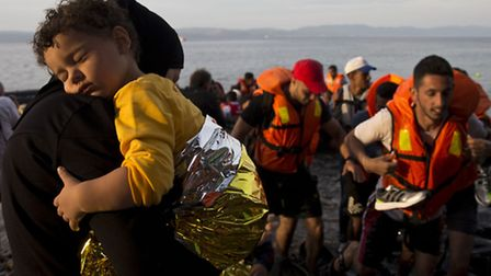 Syrian refugees arrive on a dinghy after crossing from Turkey to Lesbos island in Greece. Photo: Pet