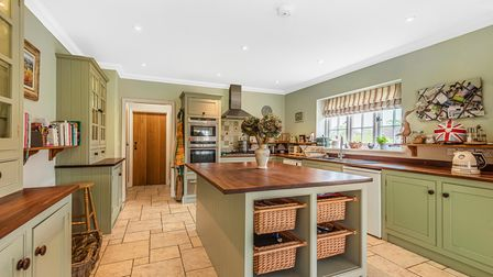Green country-style kitchen with Shaker-style units, wooden worktops, island, tiled floor