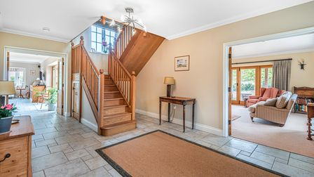 Entrance hall with wooden turning stairs leading up, door open to living room, kitchen, stone tiled floor