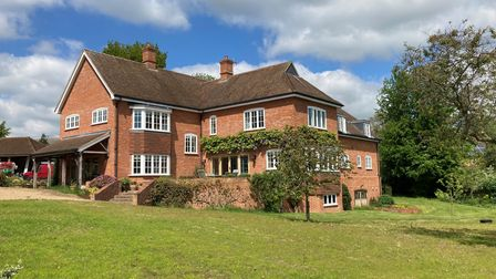 Rear of large brick-built family home with ay windows, raised patio terrace within large mature gardens