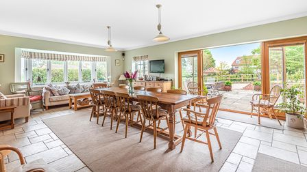 Light and airy dining area with wooden table to seat 10 and sliding doors leading outside to patio