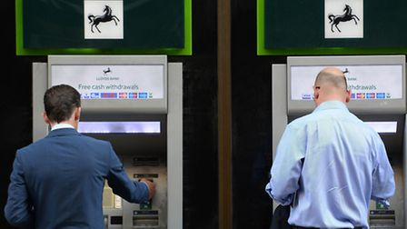Members of the public using cash machines at a branch of Lloyds Bank in the City of London. Photo: