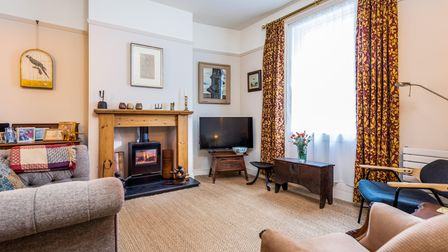 Large living room with armchair, sofa and chair on carpeted floor, TV in corner, large white sash window