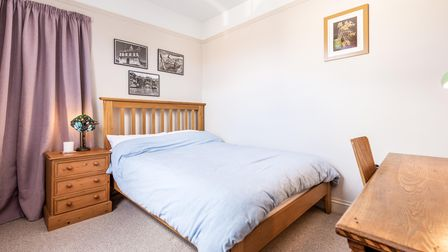 Double bedroom with carpeted floor, double bed with wooden frame, pale lilac floor-to-ceiling curtains