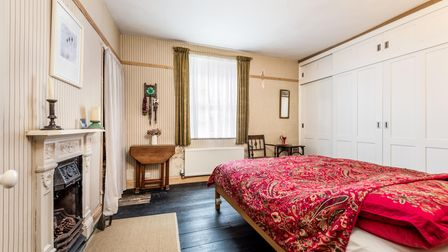 Large double bedroom with built-in wardrobes, double bed, painted floorboards and intricate feature fireplace