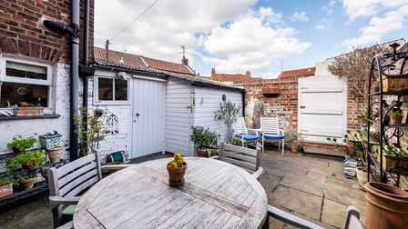Courtyard patio with timber outbuilding, table and chairs surrounded by a brick wall with a locked gate