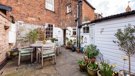Large outdoor patio courtyard with timber outbuilding, plants in pots and table and chairs