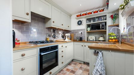 Country-style kitchen with built-in electronic appliances, wooden worktops and subway style grey tiling