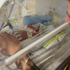 A dad with his baby in a neonatal unit