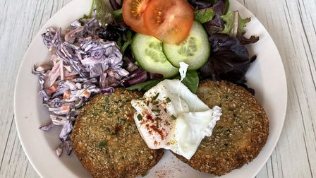 Two fishcakes topped with a poached egg, with coleslaw, salad leaves, cucumber and tomato on a white plate.