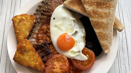 A fried breakfast with hash browns , toast, fried egg, tomatoes, mushroom, bacon, sausage and baked beans