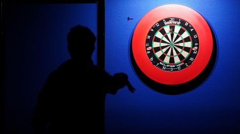 A general view of a darts board with player in silhouette