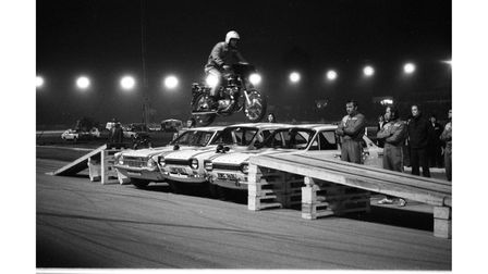 A motorcyclist rides over a row of cars in a fantastic stunt by the Canadian Auto Circus in 1973
