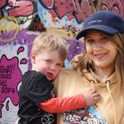 Megan Campbell, victim of domestic abuse, with her two-year-old son, Stanley, by the graffiti 'Stand