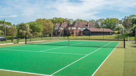 Full-size astro turf tennis court with clean line markings fenced off in front of large brick-built 1930s family home