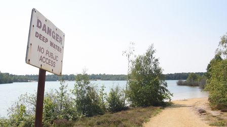 One of the warning signs at the big lake at Bawsey Pits Country Park where people are swimming and p